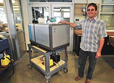 Mike Beemer standing next to a diesel generator.